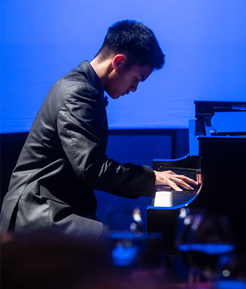 Student Plays Piano. Blue Background.