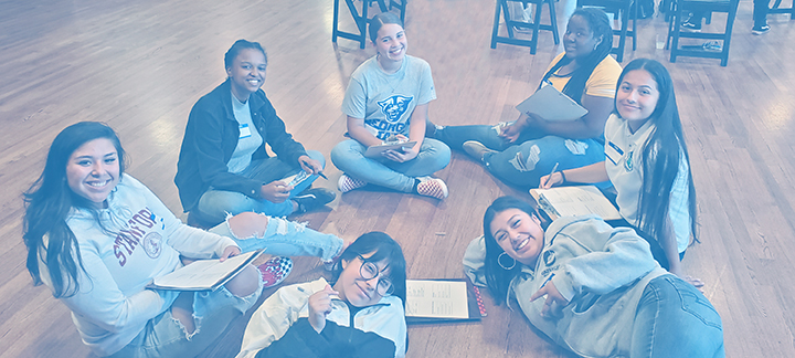 Seven students working together in a circle, smiling